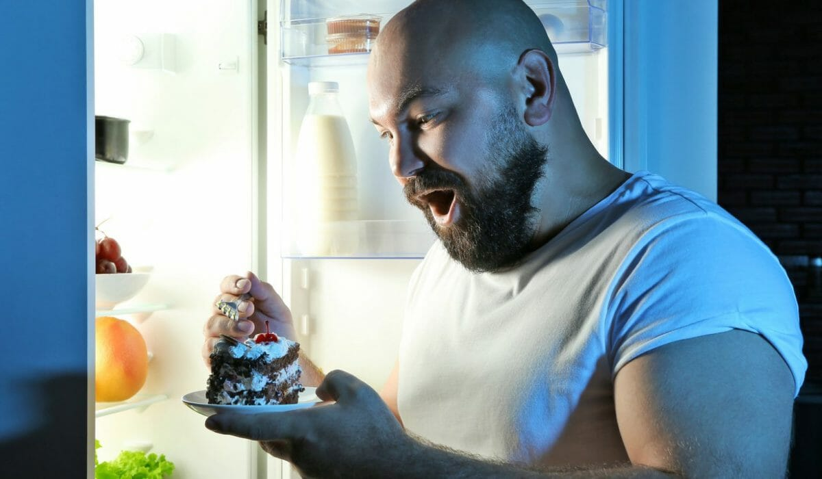 man eating at night in front of refrigerator 1