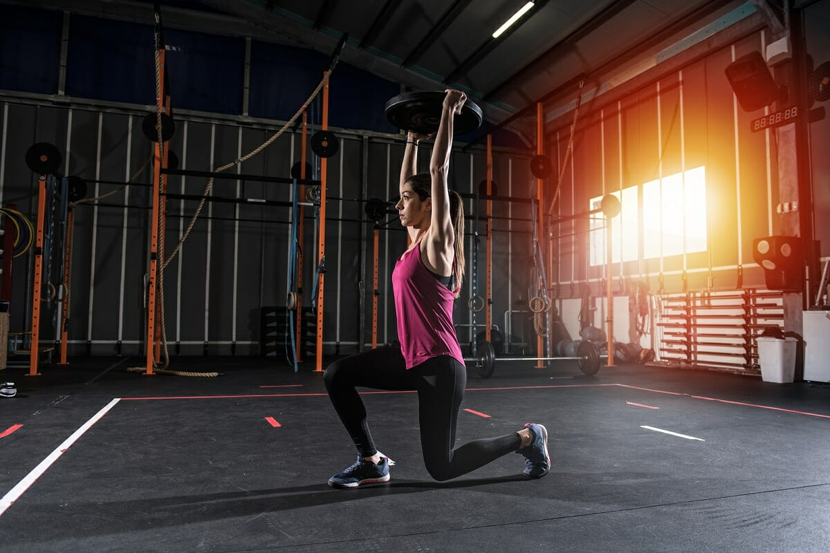 woman-split-lunging-with-weight-overhead